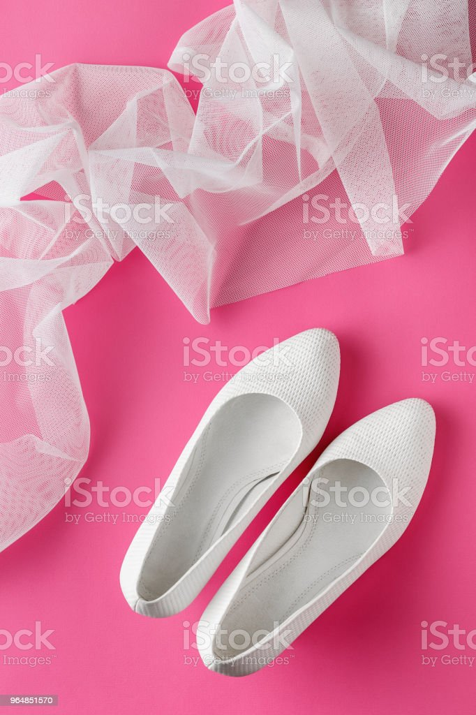 White wedding shoes on pink background royalty-free stock photo