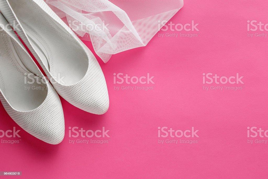 White wedding shoes on pink background royalty-free stock photo