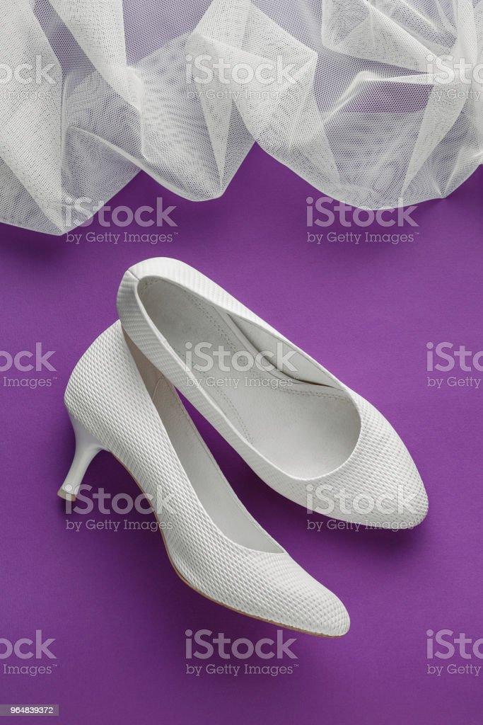 White wedding shoes on purple background royalty-free stock photo