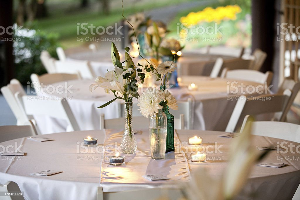 White Wedding Tables With Flowers Candels and Carafes Blurred Background stock photo