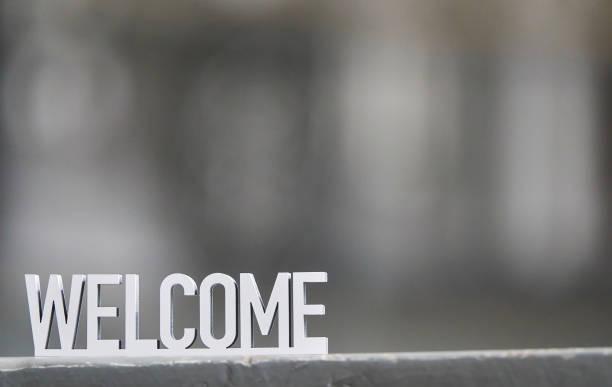 Weißes Willkommensschild auf grauem Hintergrund – Foto