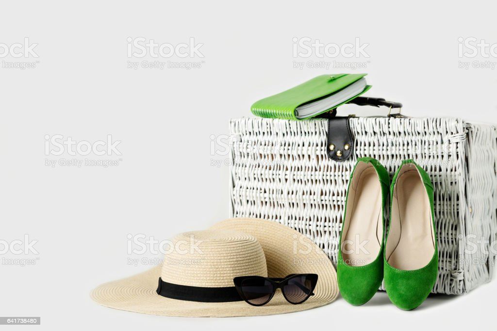 White wicker suitcase, womens hat, sunglasses, green shoes and notepad. stock photo