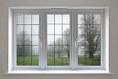 a beautifully crafted leaded glass window frame in white painted wood. The view is towards a misty  oak tree meadow in winter. This is a composite of two images.Looking for a window Please see my window collection including cut-outs with clipping paths by clicking on the Lightbox Link below...