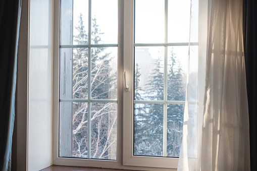 White window frame with curtain blowing by wind, winter scenic view in the morning