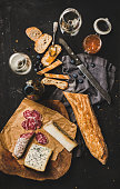 Wine and snack set. Flat-lay of sliced baguette, salami, cheese variety, apricot jam, berries and white wine over rustic black background, top view