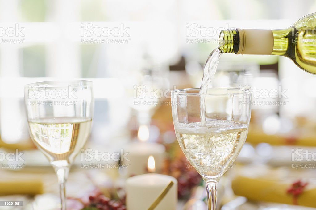 White wine being poured into glass on table stock photo