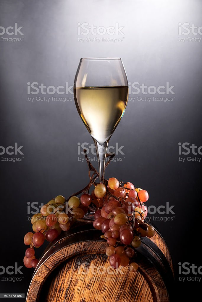 White wine glass and vine on old wooden barrel stock photo