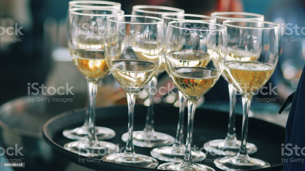 White wine glasses on a waiters tray. Waiter holds and carries out an order. Tray with glasses of alcohol drink in the restaurant stock photo