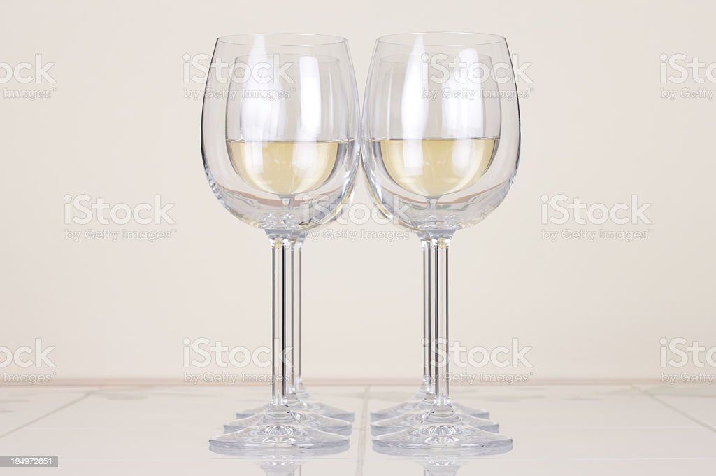 White wine glasses placed in two perfectly symmetrical rows royalty-free stock photo