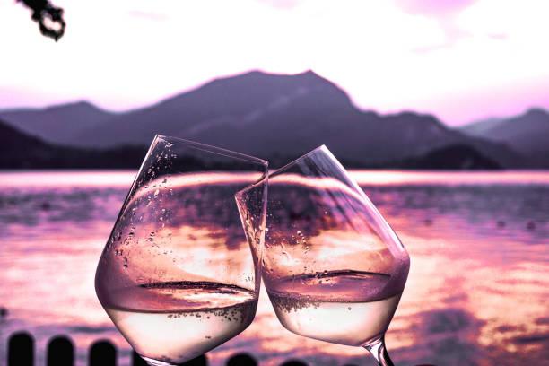 White wine glasses toasting at sunset on lake Como stock photo