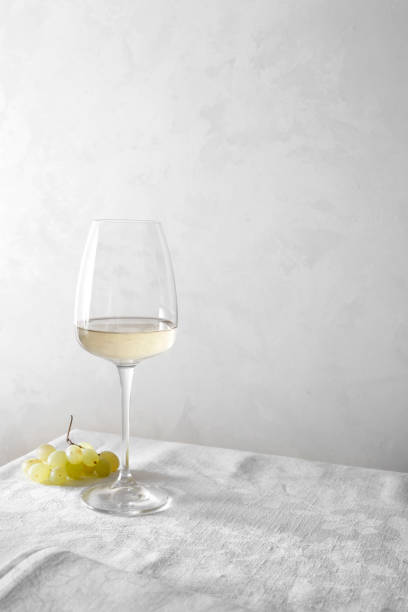 White wine in a glass and a bunch of grapes on the table. Light background. stock photo