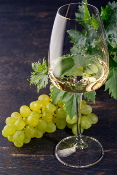 White wine in a glass and grapes on an old wooden table. Dark background. stock photo