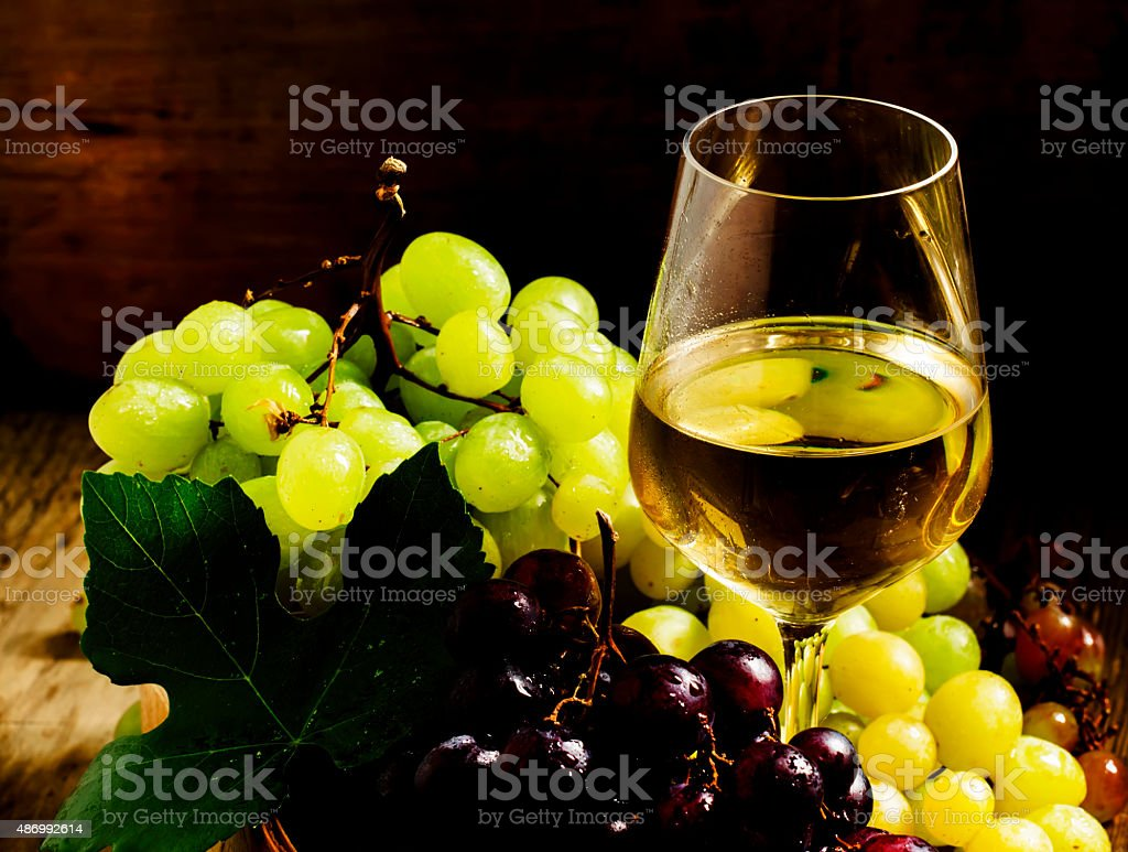 White wine in a glass and green and red grapes stock photo