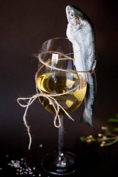 weißwein in einem glas und roher fisch an ein glas wein gebunden - b767 stock-fotos und bilder