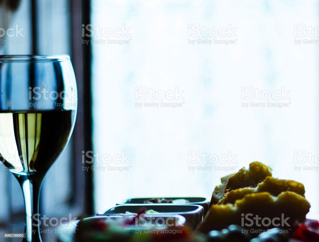 white wine in a glass with appetizers on a wooden table, a set of starters, relax with a glass of wine stock photo
