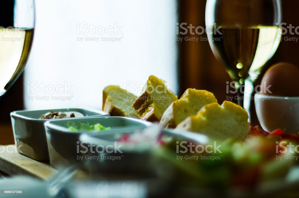 white wine in a glass with appetizers on a wooden table, a set of starters stock photo