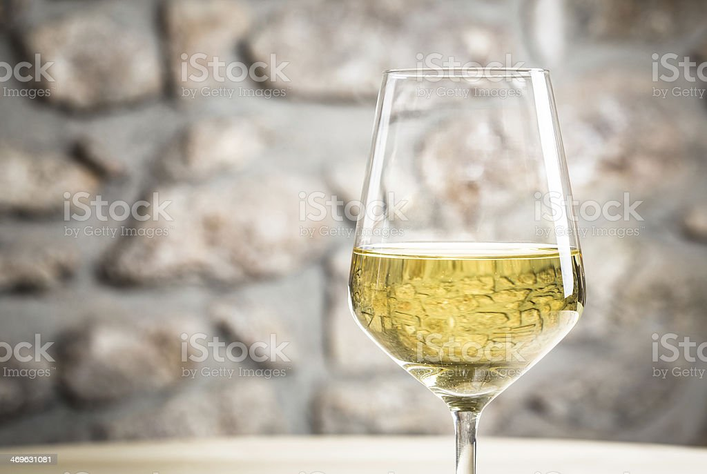 White wine in a wine glass on a table stock photo