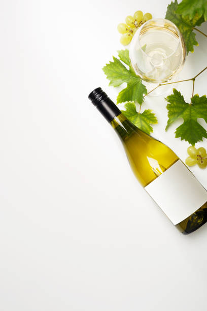 White wine in glasses, a bottle, grapes and grape leaves on the table. Bottle of white wine with label. Wine bottle mockup. Light background. stock photo