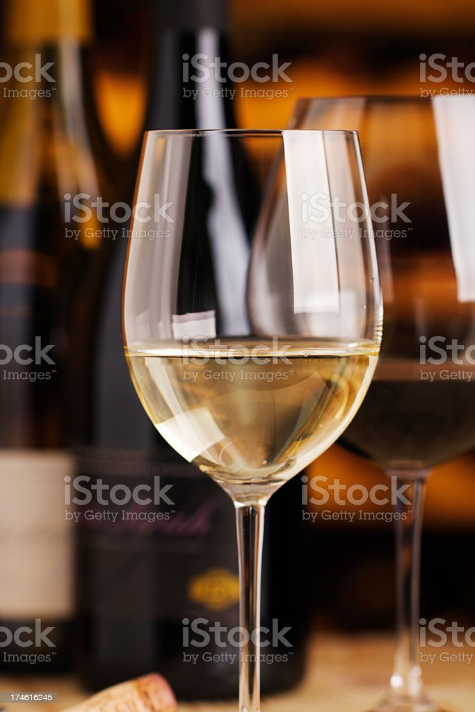 White Wine in Winetasting Glass with Cellar Bottles for Tasting royalty-free stock photo