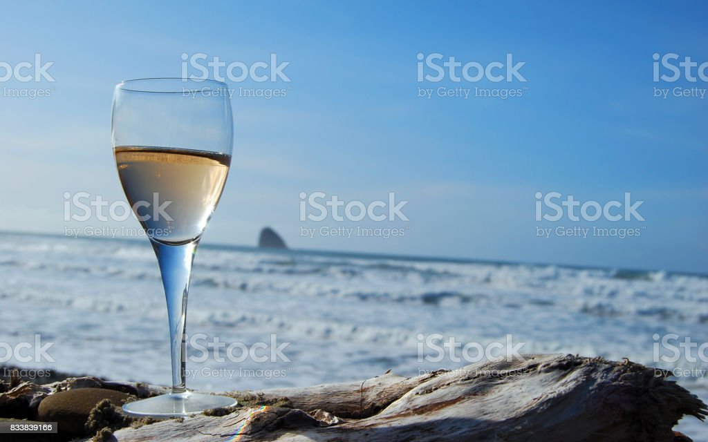 White wine on driftwood against the Pacific Ocean stock photo
