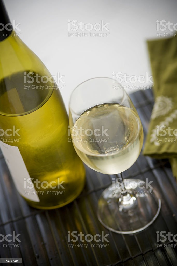 white wine on tabletop with bottle nearby royalty-free stock photo