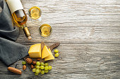 Bottle of white wine with snack food on old board. Glass of wine and cork. Wine bottle mockup. Top view