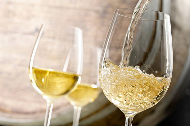 White Wine Pour Close up of white wine being poured in a cellar with an oak barrel in background. white wine stock pictures, royalty-free photos & images