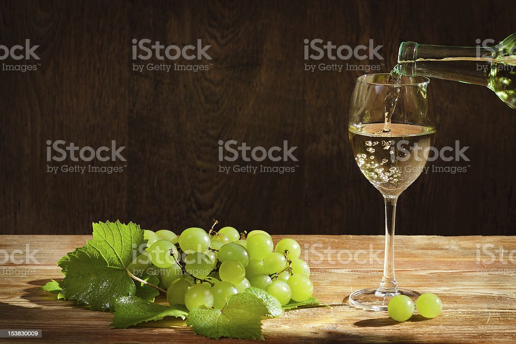 White wine pouring down to the glass royalty-free stock photo