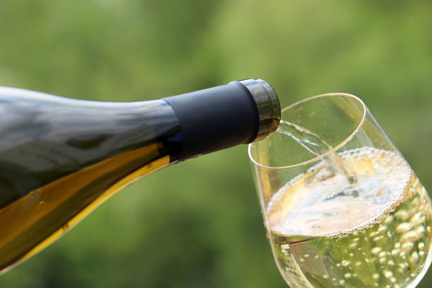 White wine pouring from the bottle into the glass on green nature blurred background Concept of celebration, party, wine drinking outdoors, champagne tasting at winery white wine stock pictures, royalty-free photos & images