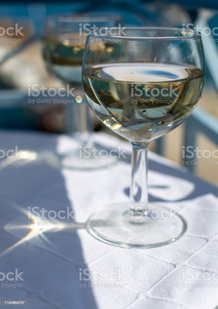 White wine served outside on balcony on glass table with sea view...