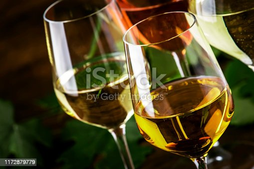 White wine set. Wine tasting, the most popular varieties of white wines in wine glasses on vintage wooden table in rustic style, selective focus