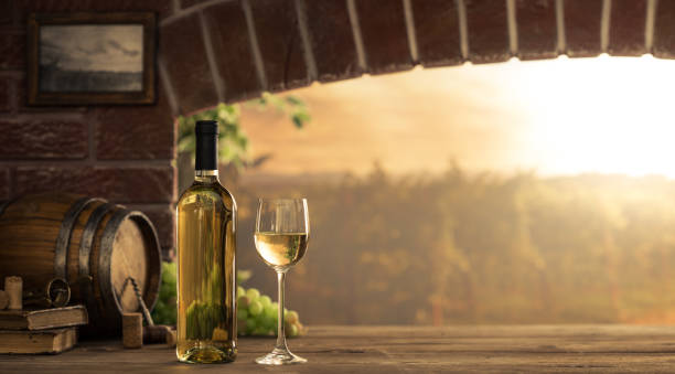 White wine tasting in the cellar White wine tasting in the wine cellar: wineglass and bottles next to the window and panoramic view of vineyards at sunset white wine stock pictures, royalty-free photos & images