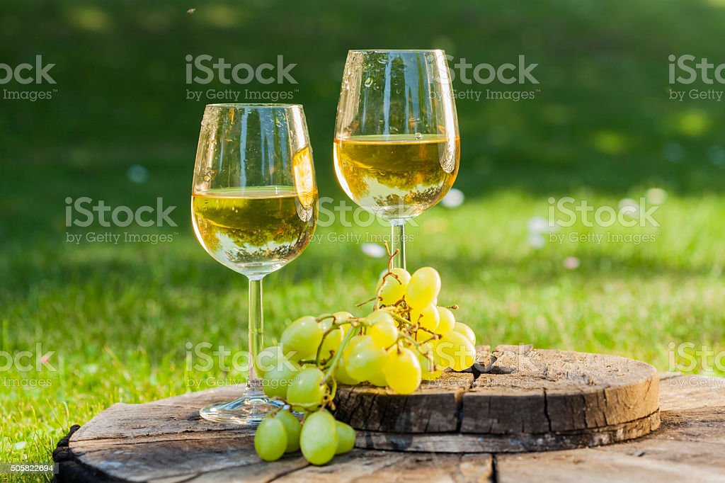 white wine with grapes on old wooden table stock photo