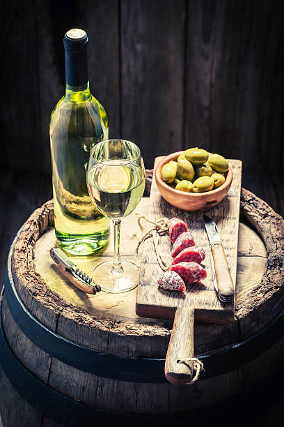 white wine with olives and cold cuts - fuet sausages fotografías e imágenes de stock
