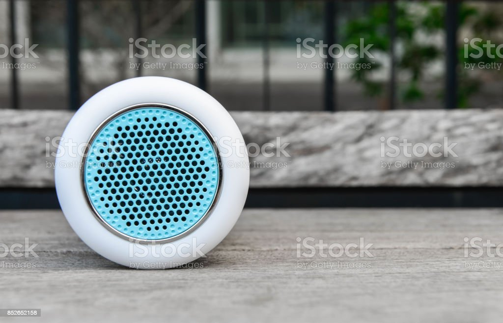 White wireless speaker on the wooden table stock photo