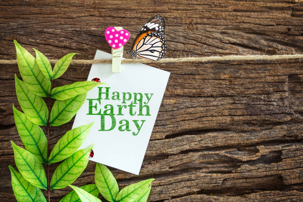 white with happy earth day paper note hanging - earth day stock pictures, royalty-free photos & images
