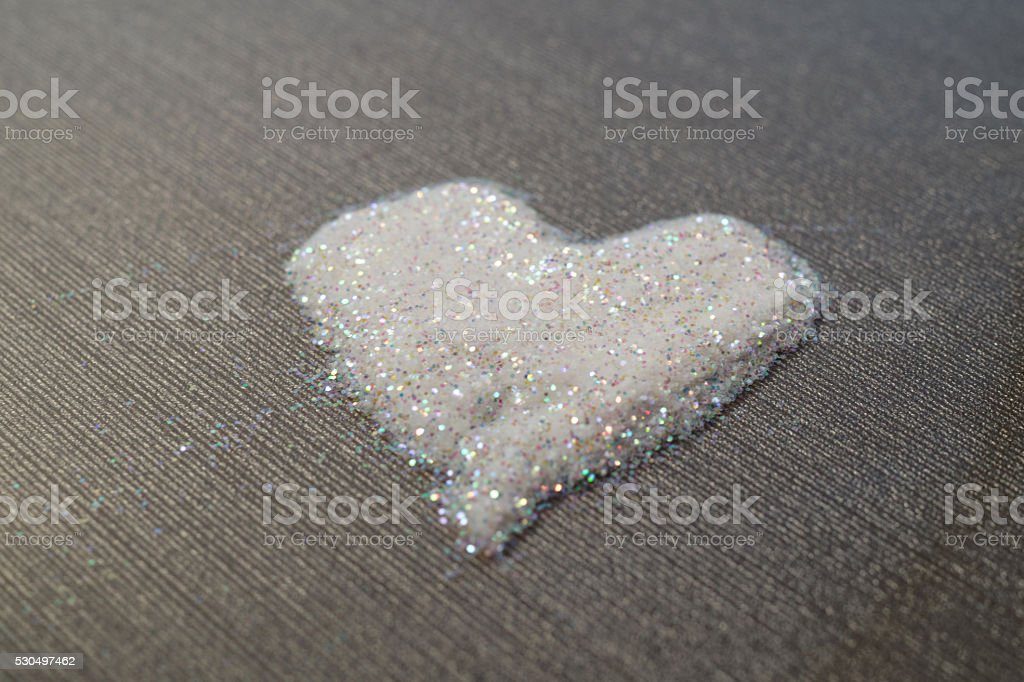 white with rainbow glitter powder heart on grey stock photo