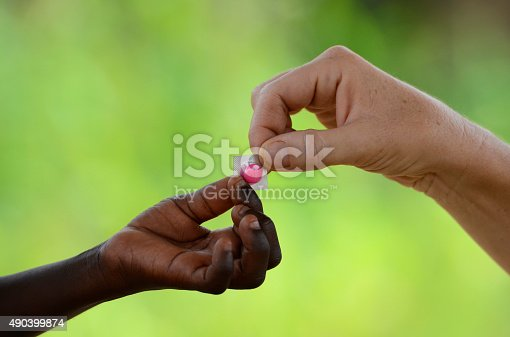 istock White Woman Gives Cure Pill to African Black Child Medicine 490399874