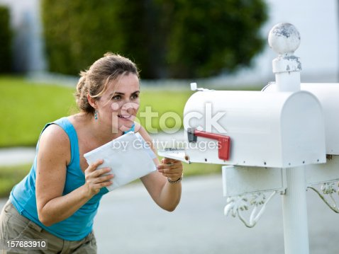 istock A white woman holding letters looks into an open mailbox 157683910