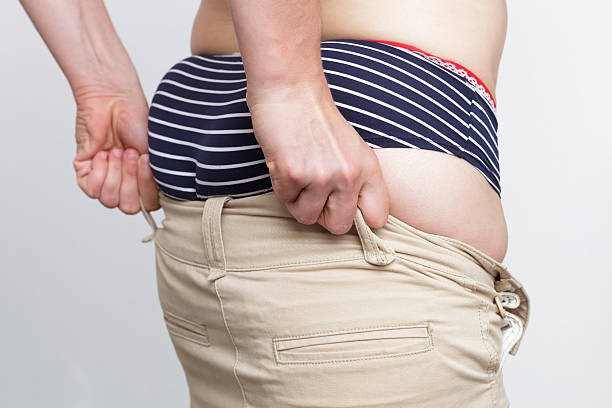 White woman trying to pull pants on a fat ass stock photo