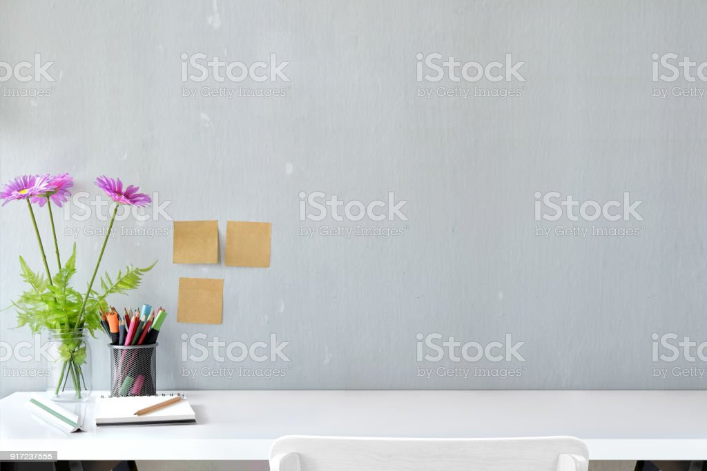 White wood desk with colour pencils, sticky note and flower with copy space.  workspace and designer accessories stock photo