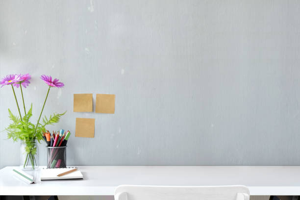 white wood desk with colour pencils, sticky note and flower with copy space.  workspace and designer accessories - desk stock photos and pictures