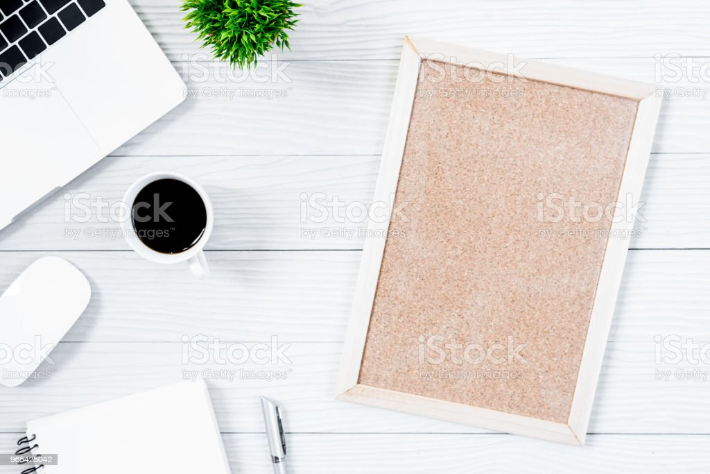 White wood office desk table and equipment for working with black coffee and blank board in top view and flat ray concept. royalty-free stock photo