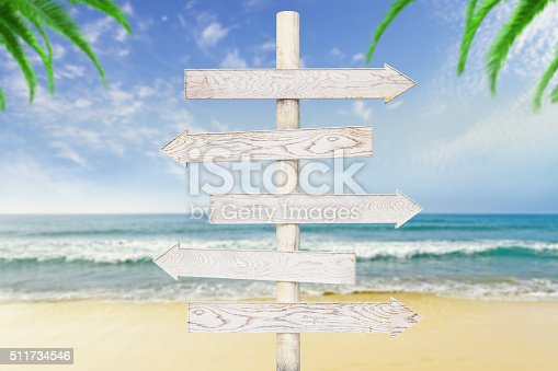 istock White wooden arrows-pointers at ocean with beach background 511734546