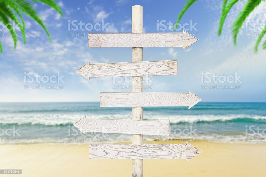 White wooden arrows-pointers at ocean with beach background stock photo