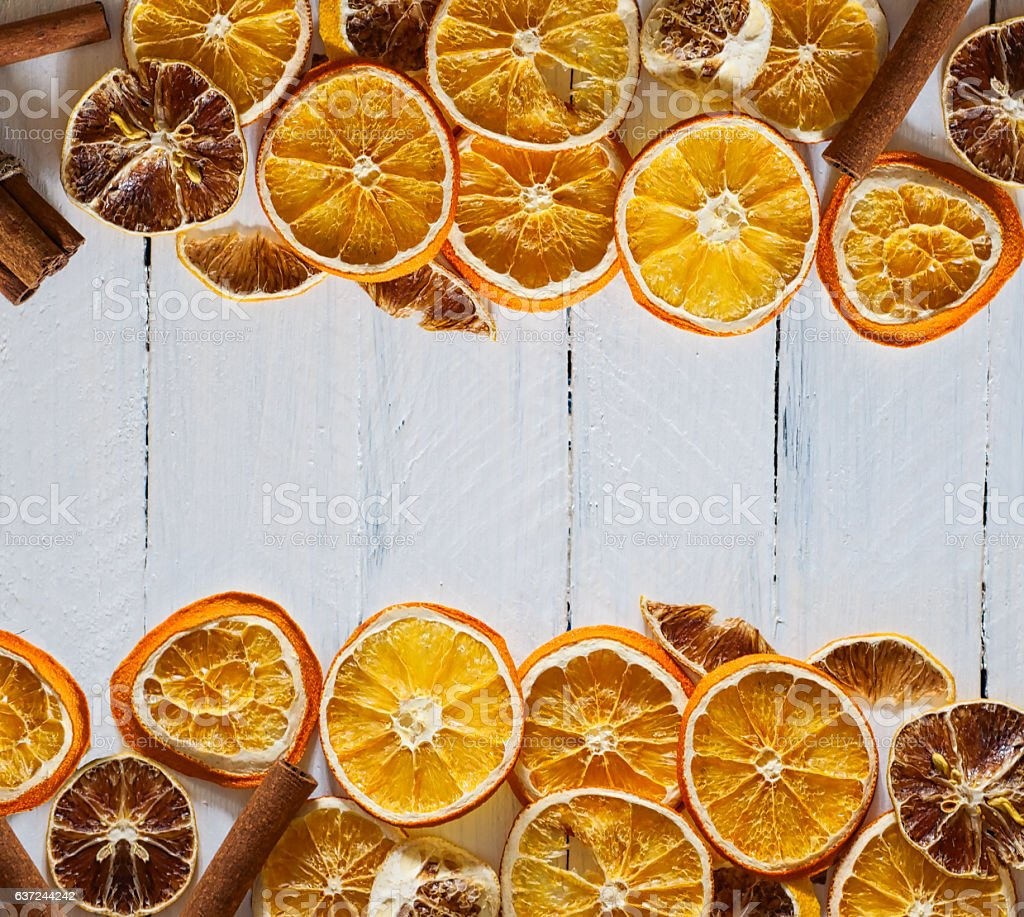 white wooden background with slices of dried orange and lemon, the...