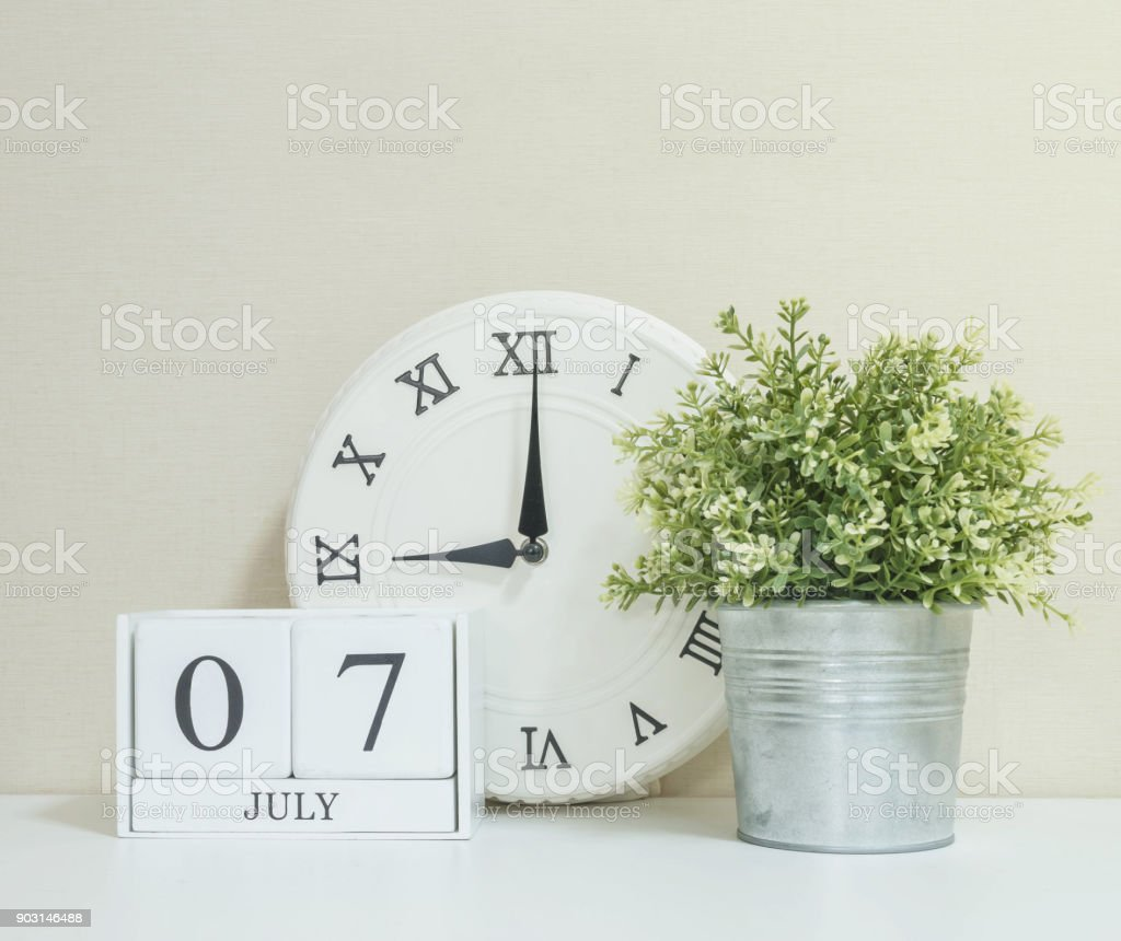 White Wooden Calendar With Black 7 July Word Clock And Plant On Wood Desk