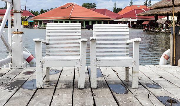 weiße holz stuhl neben den see. - pier 1 dekor stock-fotos und bilder