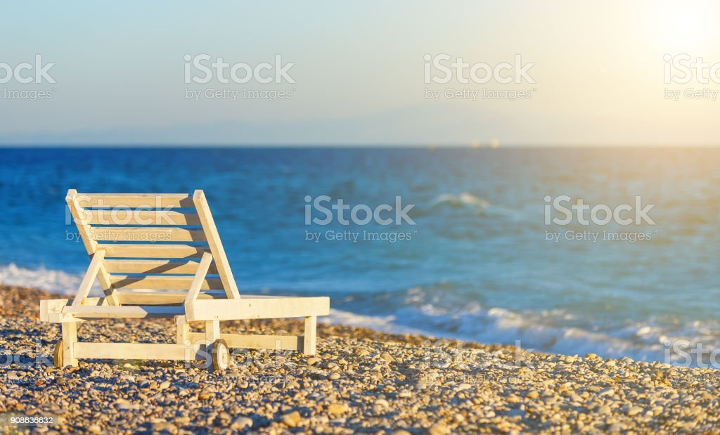 white wooden chaise longue on the shore of pebble beach at sunset, blur, depth of field stock photo