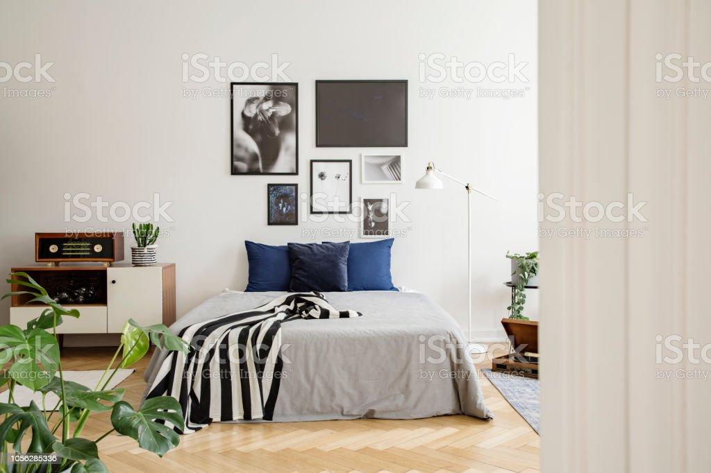 Comoda madera blanca junto a la cama con almohadas de azul for Camas blancas de madera